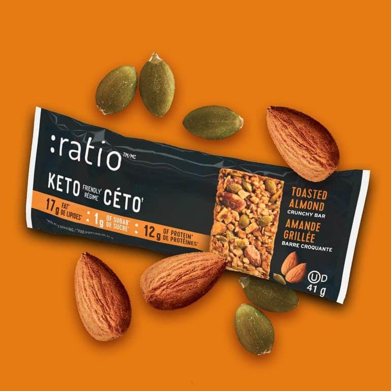 A Toasted Almond Ratio bar surrounded by almonds and pumpkin seeds on a bright orange background